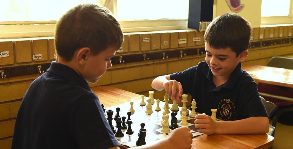 two Primary School boys playing chess against each other